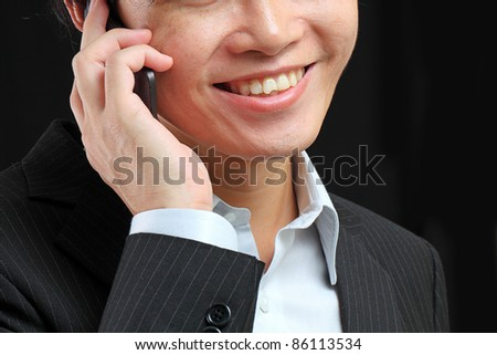 portrait of e young man talking on mobile against a black background