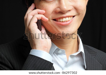 portrait of e young man talking on mobile against a black background - stock photo