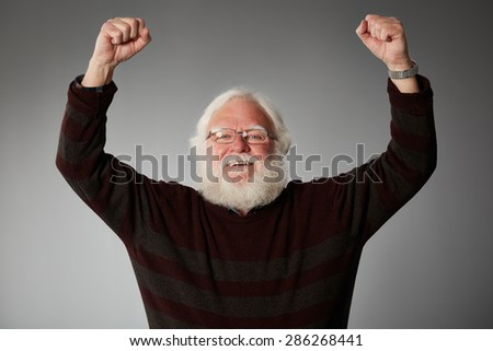 Portrait of ecstatic senior man with his arms raised against grey background - stock photo