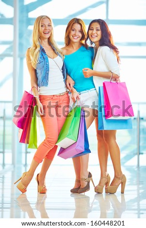 Portrait of ecstatic shoppers with paperbags posing in the mall - stock photo