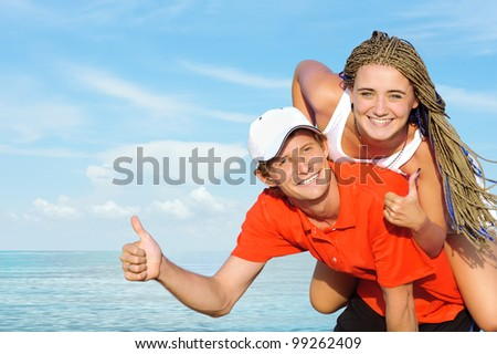 Portrait of ecstatic young couple against sea. - stock photo