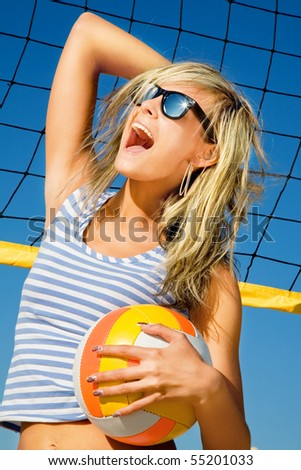 Portrait of ecstatic young girl with ball near volleyball net - stock photo