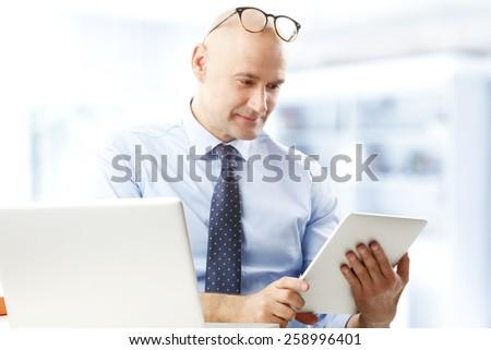 Portrait of efficiency financial advisor working at digital tablet. Businessman working. - stock photo