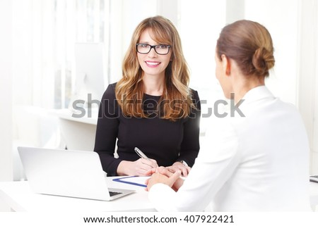 Portrait of efficient investment advisor woman sitting at desk in front of laptop and consulting with her client.