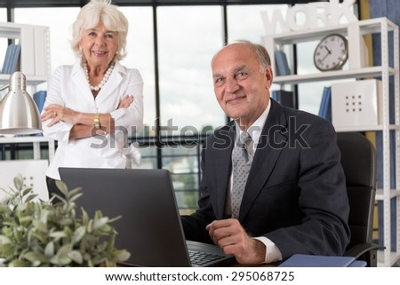 Portrait of elderly business couple in bureau