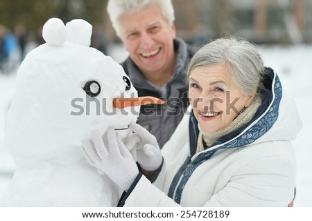 Portrait of elderly couple making snowman and shows thumbs up in winter - stock photo