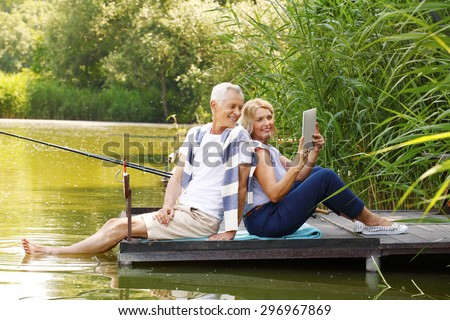 Portrait of elderly couple relaxing at nature. Senior woman and old man sitting back to back on the pier at lakeside while making self portrait with digital tablet.