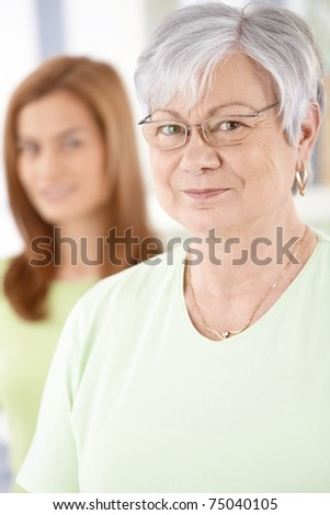 Portrait of elderly female smiling, looking at camera.?