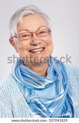 Portrait of elderly lady smiling, wearing glasses.