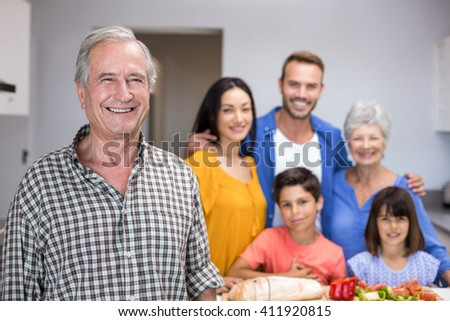 Portrait of elderly man in the kitchen and other family member standing in background - stock photo