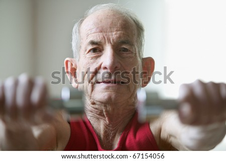 Portrait of elderly man lifting weights - stock photo