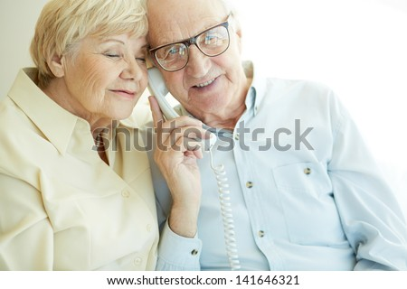 Portrait of elderly man looking at camera awhile talking on the phone with his wife near by - stock photo