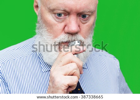 Portrait of elderly man speaking to voice recorder on green background, color and contrast manipulated - stock photo