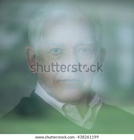Portrait of elderly man with mental illness - stock photo