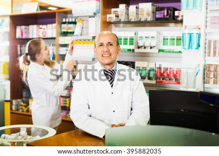 Portrait of elderly pharmacist and young assistant working at farmacy reception - stock photo