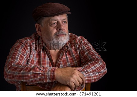 Portrait of elderly Ukrainian peasant wearing checked shirt and peaked cap in low key - stock photo