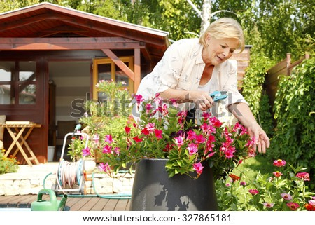 Portrait of elderly woman gardening at home. Retired female care for your plants in her beautiful garden.