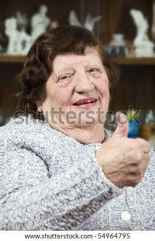 Portrait of elderly woman giving thumbs up and smiling in her living room