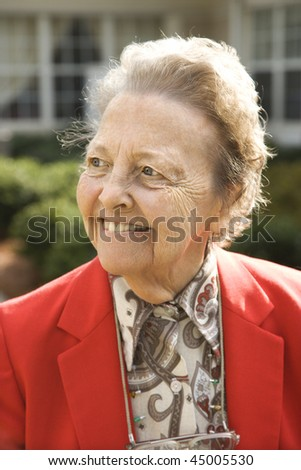 Portrait of elderly woman in red coat smiling to the side. Vertical shot. - stock photo