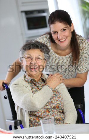 Portrait of elderly woman in wheelchair with homecarer - stock photo