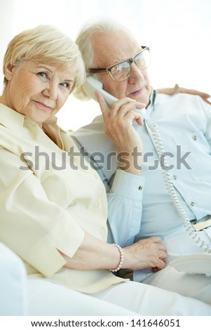 Portrait of elderly woman looking at camera with her husband talking on the phone near by - stock photo