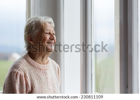 Portrait of Elderly woman looking out window, Grandmother smiling - stock photo