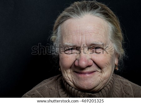 Portrait of elderly woman on dark background.