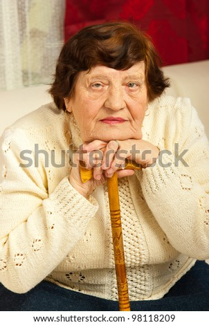 Portrait of elderly woman resting her face on hands with wood cane and sitting on couch in her home - stock photo
