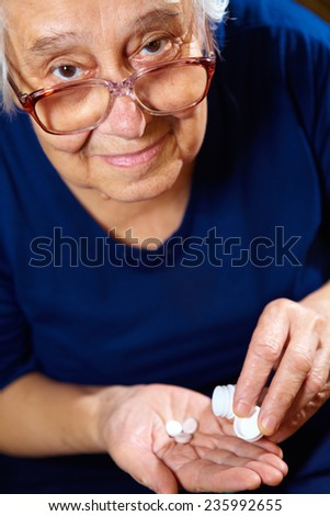 Portrait of elderly woman with pills. Health care - stock photo