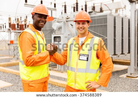 portrait of electrical engineers working together in substation - stock photo