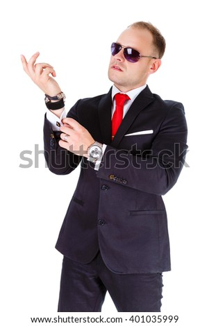 Portrait of elegant and stylish business man in black suit, red tie and black sunglasses, adjusts his cufflinks - isolated on white background. concept of leadership - stock photo