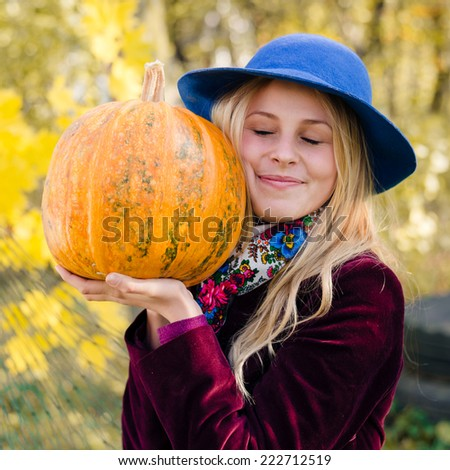 portrait of elegant beautiful blond young woman having fun holding pumpkin happy smiling eyes closed on autumn copy space outdoors background - stock photo