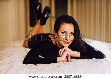 Portrait of elegant beautiful brunette woman lying in bed in a black dress, looking at camera. - stock photo