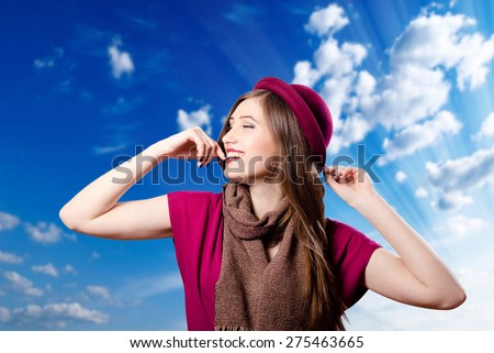 Portrait of elegant beautiful smiling woman in red hat on blue sky copy space background - stock photo