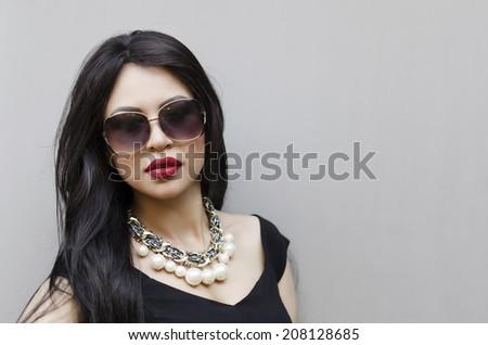 Portrait of elegant beautiful woman wearing black dress and sunglasses - stock photo