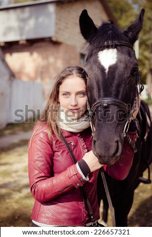 portrait of elegant beautiful young woman embracing horse smiling on autumn copy space outdoors background - stock photo