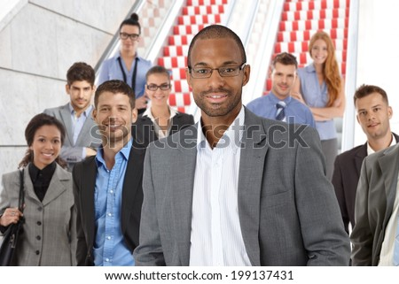 Portrait of elegant black businessman, young businesspeople at background.