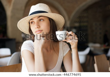 Portrait of elegant brunette beauty having espresso coffee.
