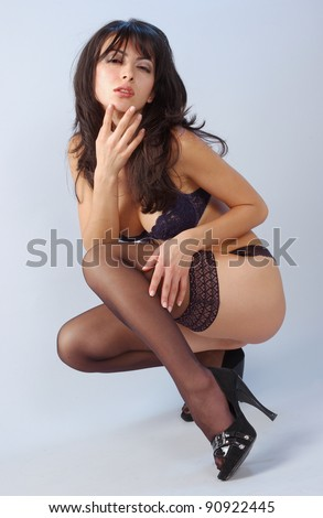 portrait of elegant brunette woman in black sexy lingerie,gloves, stockings and shoes, sitting on isolated grey background. - stock photo