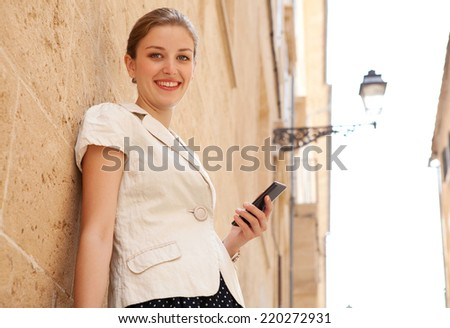 Portrait of elegant business woman in a classic city with textured stone buildings and walls, holding a high technology smartphone in her hand, smiling at the camera outdoors. People and technology. - stock photo