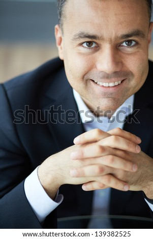 Portrait of elegant businessman looking at camera with smile - stock photo