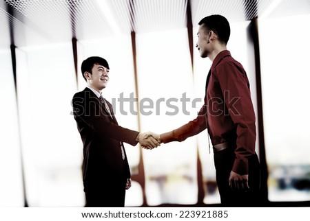 Portrait of elegant businessmen handshaking in conference hall - stock photo