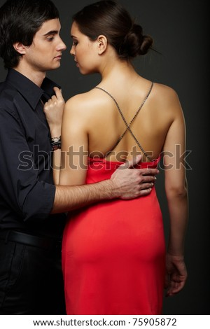 Portrait of elegant couple on black background - stock photo