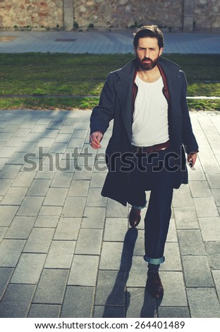 Portrait of elegant fashionable adult man dressed in coat walking in urban setting, stylish hipster man walking on the street at sunny evening, filter - stock photo