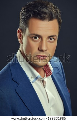 Portrait of elegant handsome businessman in blue suit looking confidently at the camera over dark background. Smart successful people. - stock photo