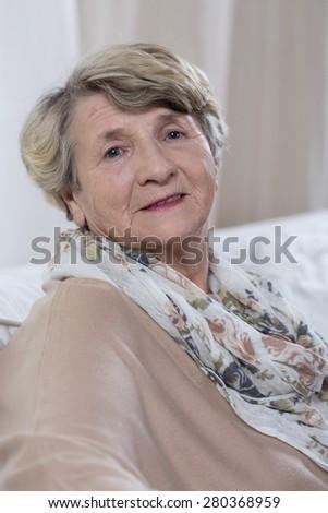 Portrait of elegant happy senior lady sitting at home - stock photo
