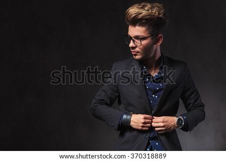 portrait of elegant man fixing his jacket in dark studio background. he is wearing glasses while looking away.  - stock photo
