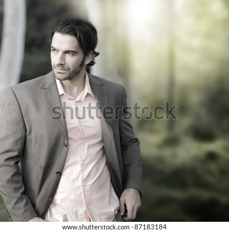 Portrait of elegant man in suit outdoors with lots of copy space - stock photo