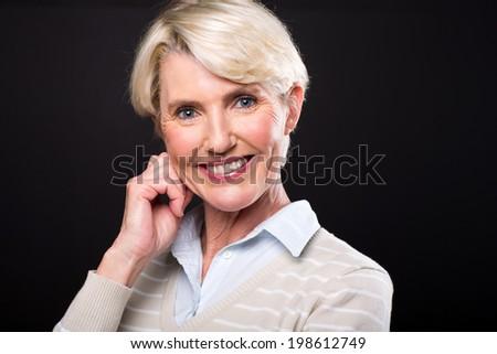 portrait of elegant mature woman over black background - stock photo