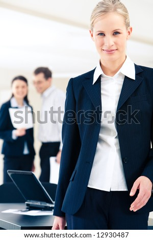 Portrait of elegant woman in suit standing on the background of two working people - stock photo